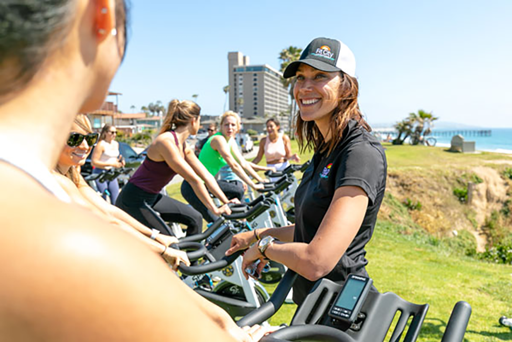 Fit City leader interacting with the outdoor spin class