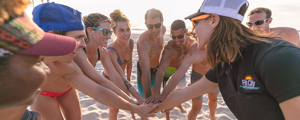 Fit City team in huddle at the beach with arms reaching out