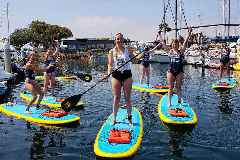Group of young woman paddleboarding in the harbor