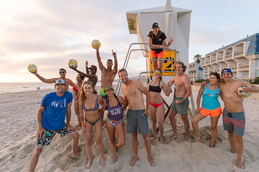 Group shot of Fit City volleyball players at lifeguard stand on the beach