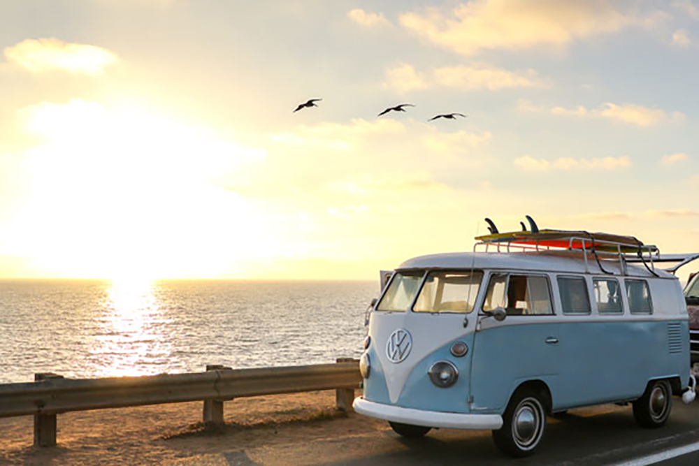 Old VW Surf van with surfboards on top parked along side of road looking out at ocean at sunset