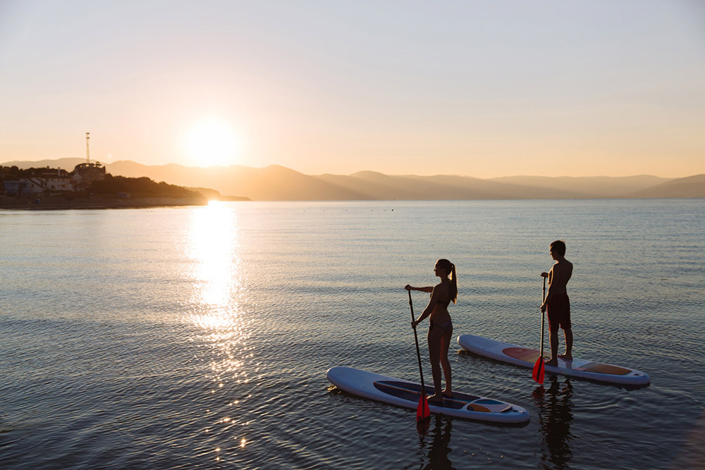 Young man and woman standing on surf board in calm waters watching the sun set