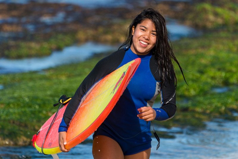 attractive young female walking in the water holding a surf board