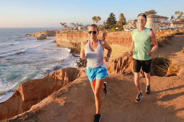 young male and female running along the cliffs overlooking the San Diego shore