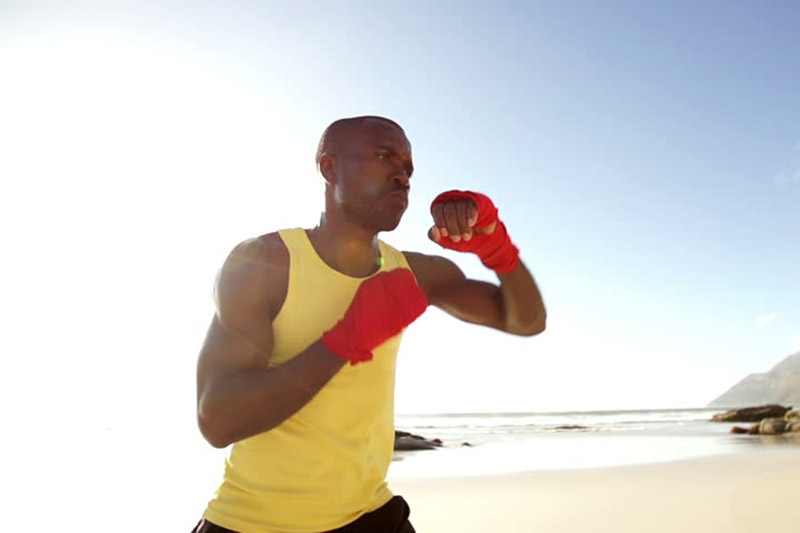 young man shadow boxing on the beach