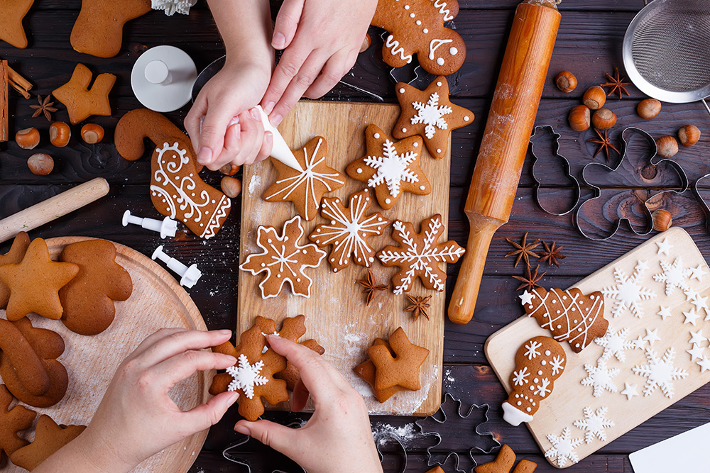 Friends decorating freshly baked gingerbread cookies with icing and confectionery mastic