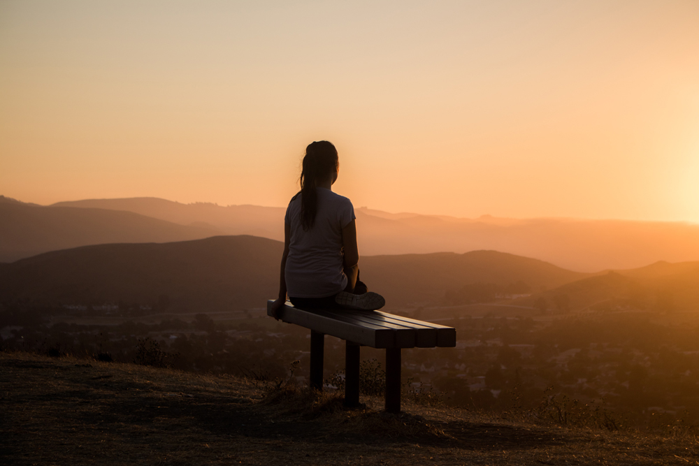 woman sitting on a bench watching the sunrise